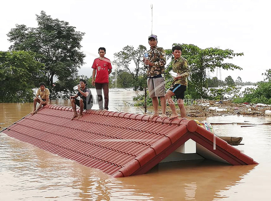 Villagers take refuge on a rooftop above floodwaters from a collapsed dam in the Attapeu district of southeastern Laos, Tuesday.