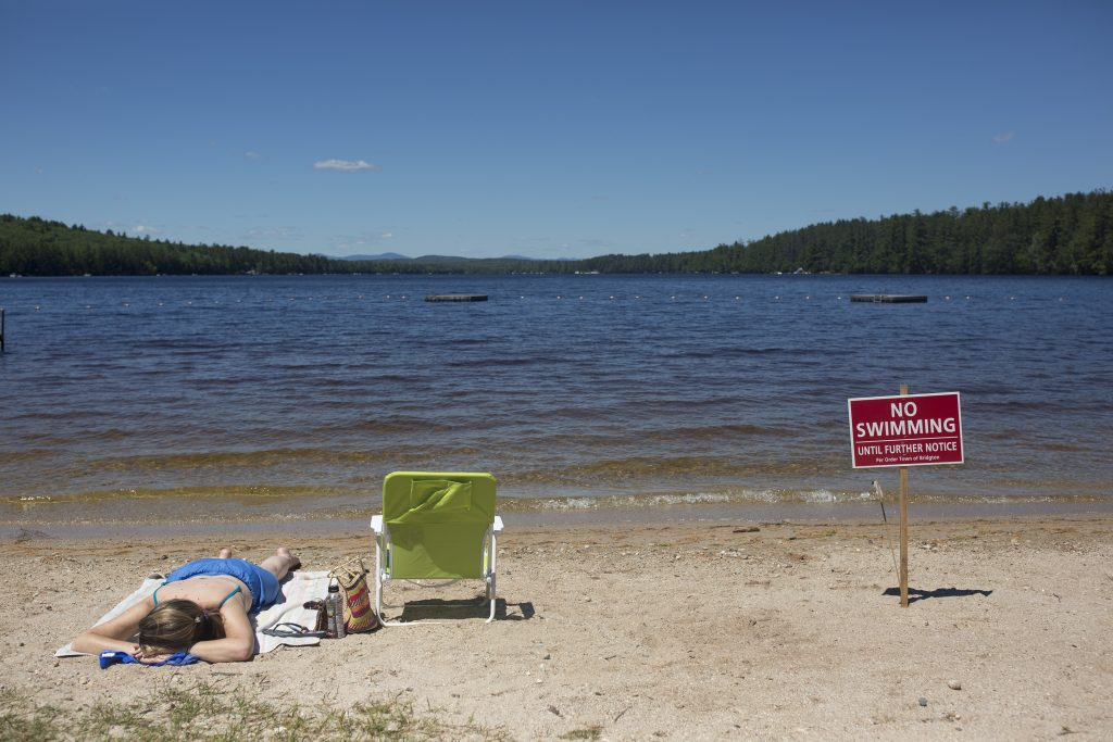 Christy Dow sunbathes on Woods Pond Beach next to one of the no swimming signs that line the sand. Dow, of Naples, said she didn't know about the swimming ban until she saw the sign and said she had driven by the beach in hopes of sunbathing on Thursday, but decided it was too busy.