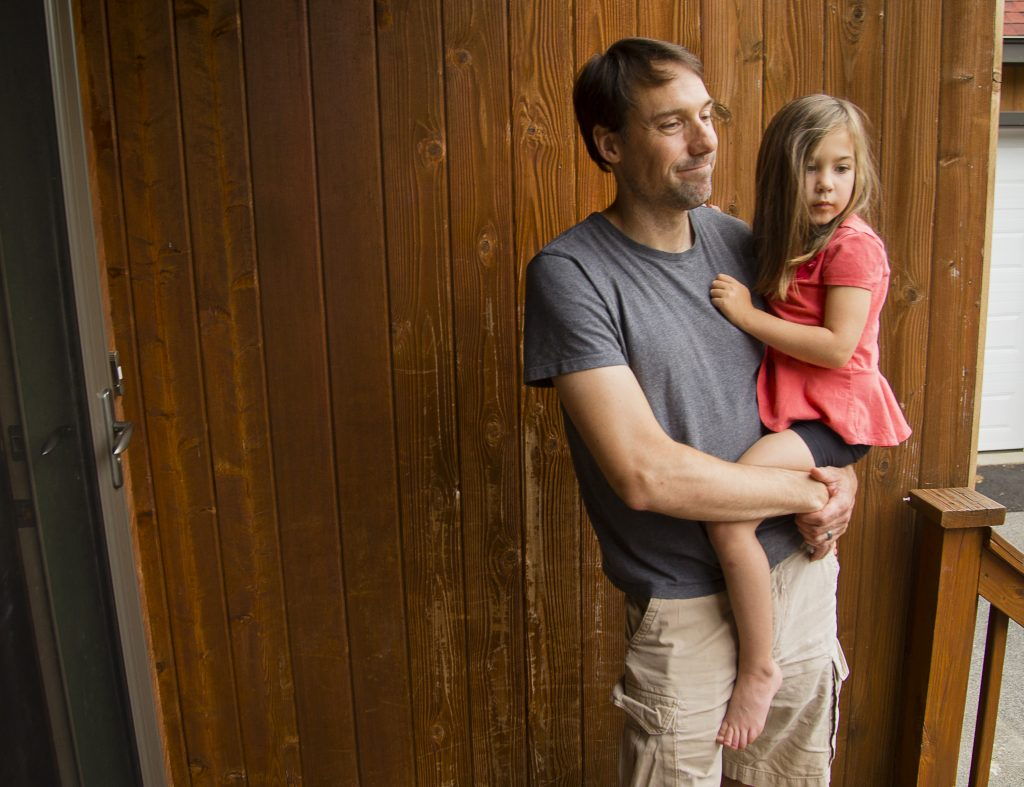 Alex Hallet, with daughter Sybil, talks Monday about witnessing and photographing the fox that came through his yard and also bit at least three of his neighbors on Friday. He was aware of the fox's biting activity in the neighborhood and had his children and pets safely inside when he photographed it from an upstairs window.