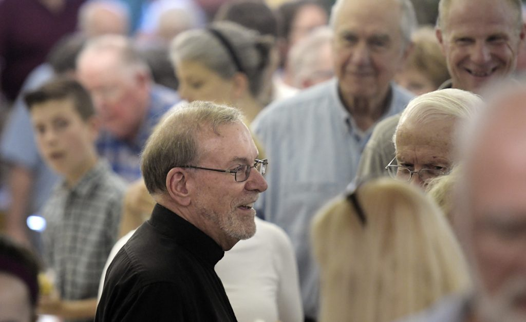 Hundreds come to give the Rev. Francis Morin, center, well wishes Sunday in the basement of St. Augustine's Church in Augusta before his retirement.