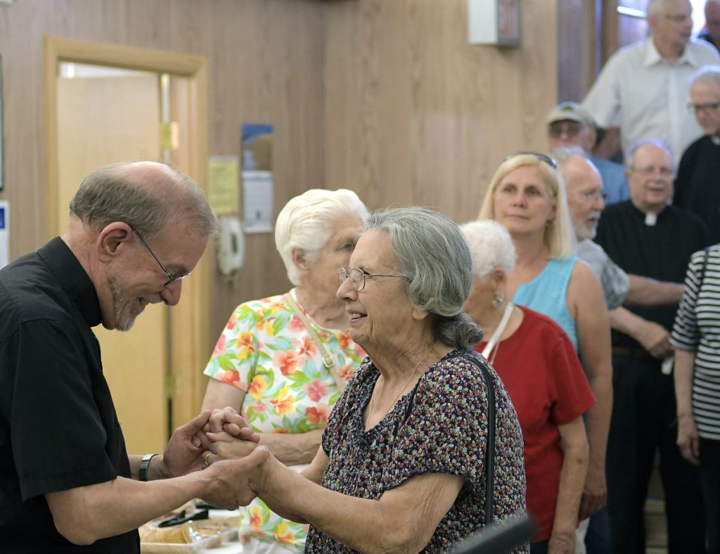 Hundreds crowd into the basement of St. Augustine's Church on Sunday in Augusta to wish the Rev. Francis Morin, or Father Frank, left, well in retirement. The former head of St. Michael Parish, which oversees a handful of Catholic churches in Augusta, Winthrop, Gardiner, Whitefield and Hallowell, is retiring after nine years in Augusta and a lifetime of priestly duties. He's known for reaching out to immigrants and others in need and other social justice efforts.
