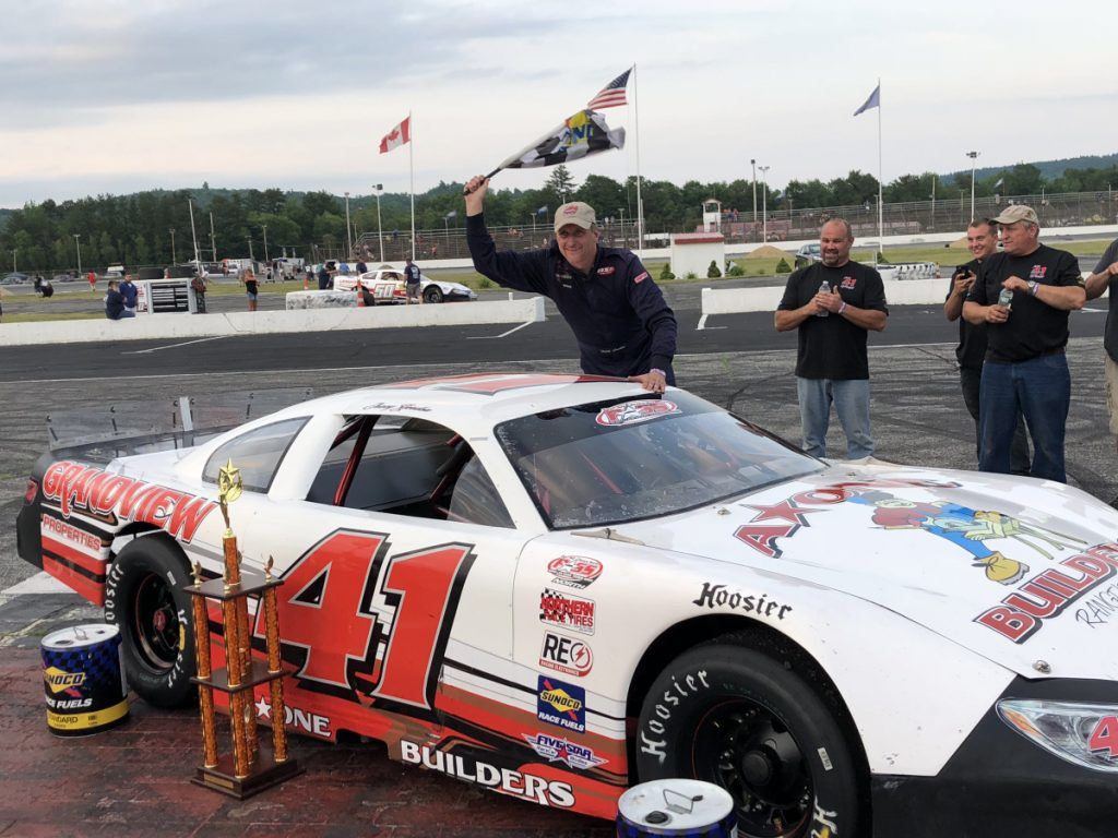 Tracy Gordon waves the checkered flag after winning the PASS Open 100 on Sunday at Oxford Plains Speedway.