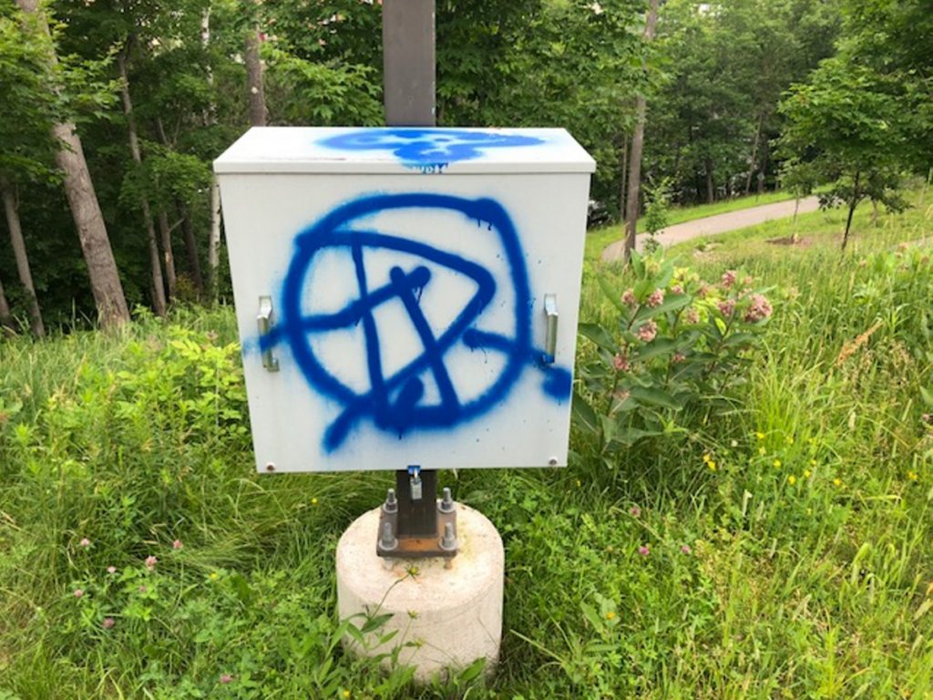 Graffiti on a utility box along the Debe Park River Trail in Skowhegan is one of several locations hit with spray paint sometime over the weekend. The trail ends at a Joyce Street house, where a man was shot in the head with a pellet gun on Sunday. Police are uncertain if the vandalism is connected to the shooting incident.