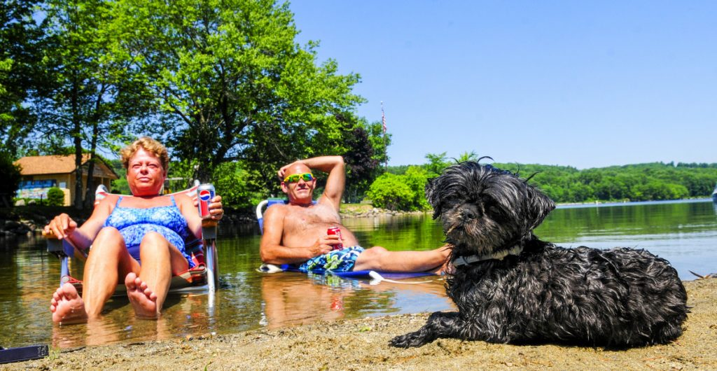 Tina Tarbox, left, David Tarbox and their dog Deliah cool off in Maranacook Lake in Winthrop on Thursday, as the temperature soared above 90 degrees. The nearby town beach was crowded too as people tried to beat the heat.