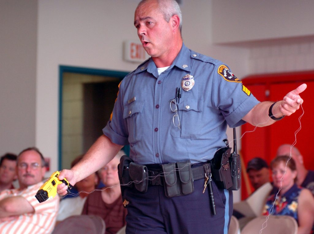 Dan Cook, seen in 2015 when he was a sergeant with the Winthrop Police Department, collects the coils of a Taser after discharging the weapon during a demonstration at a town council meeting. Cook has been serving as interim police chief for about a year and is retiring this month after a 25-year police career.