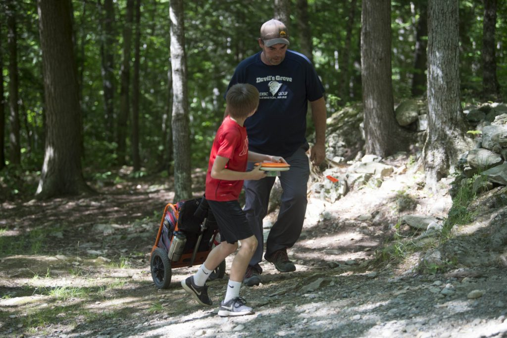 Nate Delisle, 11, gets some pointers from his caddie Bobby Harris during a Pro Disc Golf Association qualifier at Burnsboro Disc Golf Course on Saturday in Vassalboro.