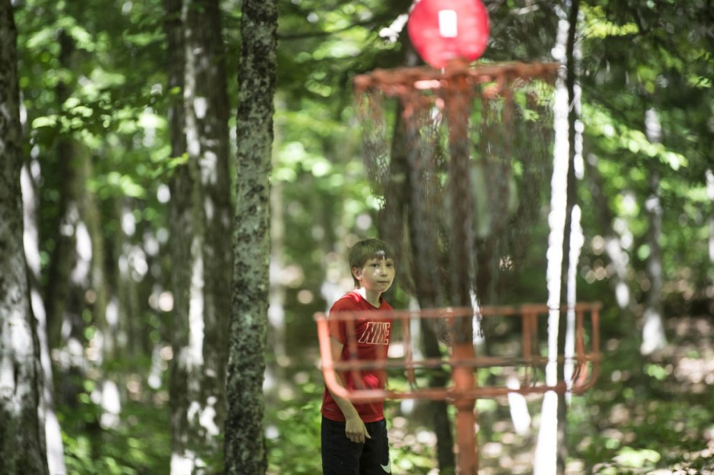 Nate Delisle, 11, sinks his putt during a Pro Disc Golf Association qualifier at Burnsboro Disc Golf Course on Saturday in Vassalboro.