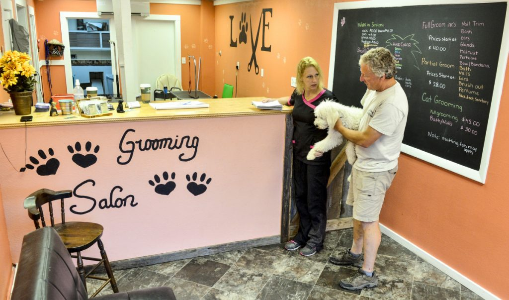 Melanie Hubble talks with Eric Guilt about how he wants her to groom his dog, Sam, on Friday at Wagging Tails Grooming Salon on Main Street in Winthrop.