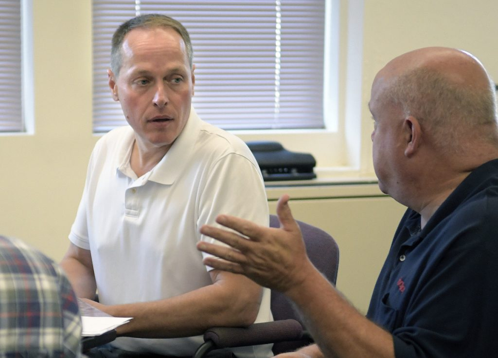 Winthrop Town Manager Ryan Frost, left, meets with town officials, including Fire Chief Dan Brooks, on Tuesday at the Town Hall. Winthrop Town Manager Ryan Frost plans to return to the position of police chief, after having left that job a year ago to take the town manager's position.