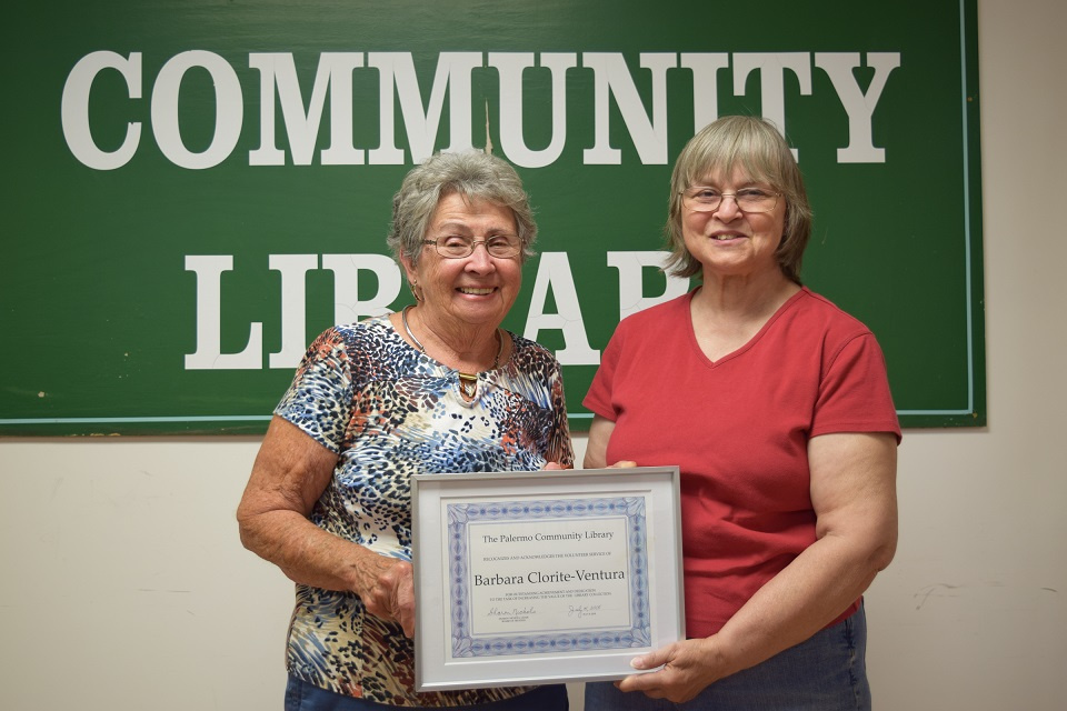 Palermo Community Library Board of Trustees Chair Sharon Nichols, left, recognizes Barbara Clorite-Ventura, a library volunteer, for her dedication in correcting the value of the Library's collection.