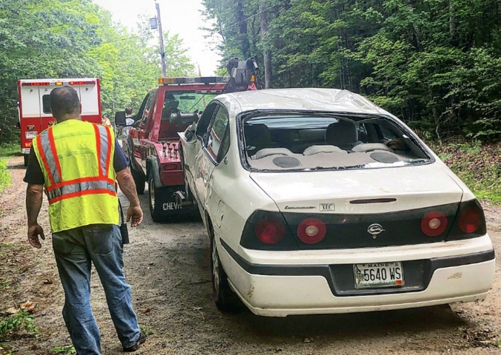 Smithfield Fire Chief Jack Easler stands next to a Chevrolet Impala on Thursday morning that was involved in a rollover accident on Wilder Hill Road in Smithfield. Police think the crash was caused by the driver traveling at an excessive rate of speed.