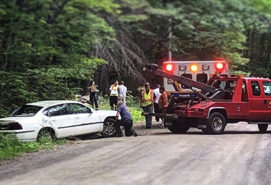 A crew works to pull a Chevrolet Impala out of a ditch Thursday morning on Wilder Hill Road in Smithfield after a crash. Kane Grondin, 17, who was driving the vehicle at the time of the crash, has been charged with imprudent speeding and carrying passengers with an intermediate license.