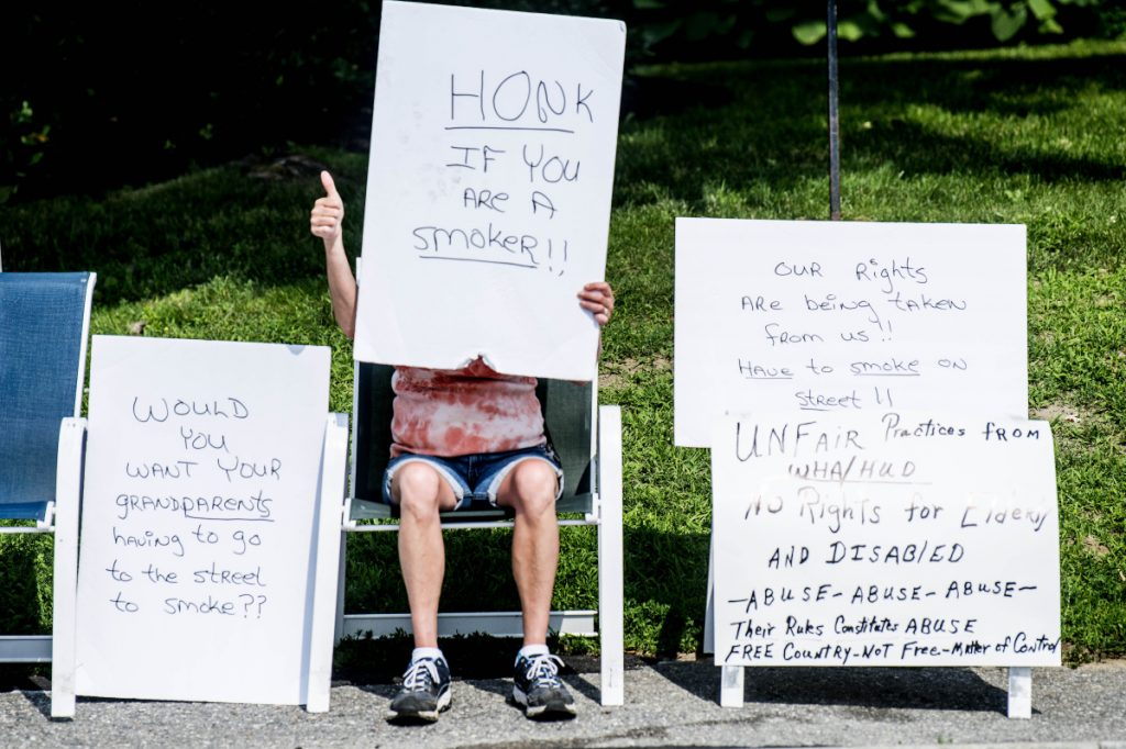 Misty LaCroix, a resident of the Elm Towers, gives the thumbs-up sign July 3 to a pro-smoking horn honker for supporting her protest of a smoking ban recently instituted by Waterville Housing Authority.