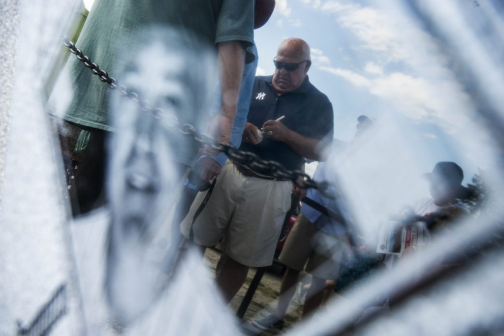 Former New York Yankees manager Stump Merrill signs autographs as he is reflected in a honorary plaque during opening ceremonies for the Cal Ripken 12U New England regional tournament Friday at Purnell Wrigley Field in Waterville.