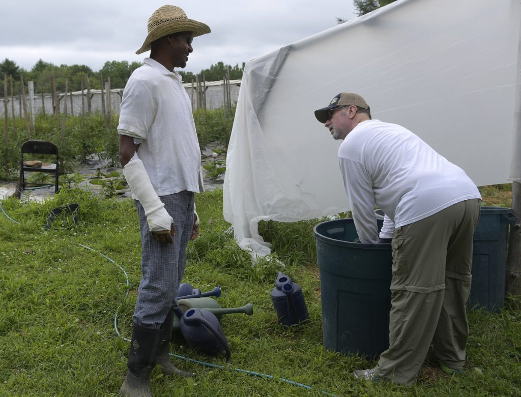 Craig Hickman, left, speaks Sunday with his neighbor, John Branning, who volunteered to fertilize vegetables at the Winthrop farm Hickman operates with his husband, Jop Blom. Hickman is welcoming the assistance of volunteers at Annabessacook Farm while he recovers from burns he sustained last week.