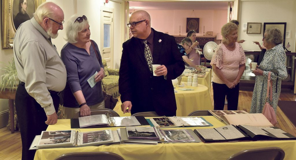 First Baptist Church pastor Russell LaFlamme, right, shows some historical photos of the church to Pastor Ronald Morrell of China Baptist Church and his wife, Linda, during the 200th anniversary celebration on Sunday.