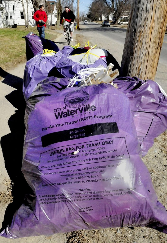 Purple bags of trash used in the pay-as-you-throw trash program in Waterville sit curbside for pick up on Western Avenue on April 15, 2015. The City Council will consider extending an agreement with the bag supplier for another two years.