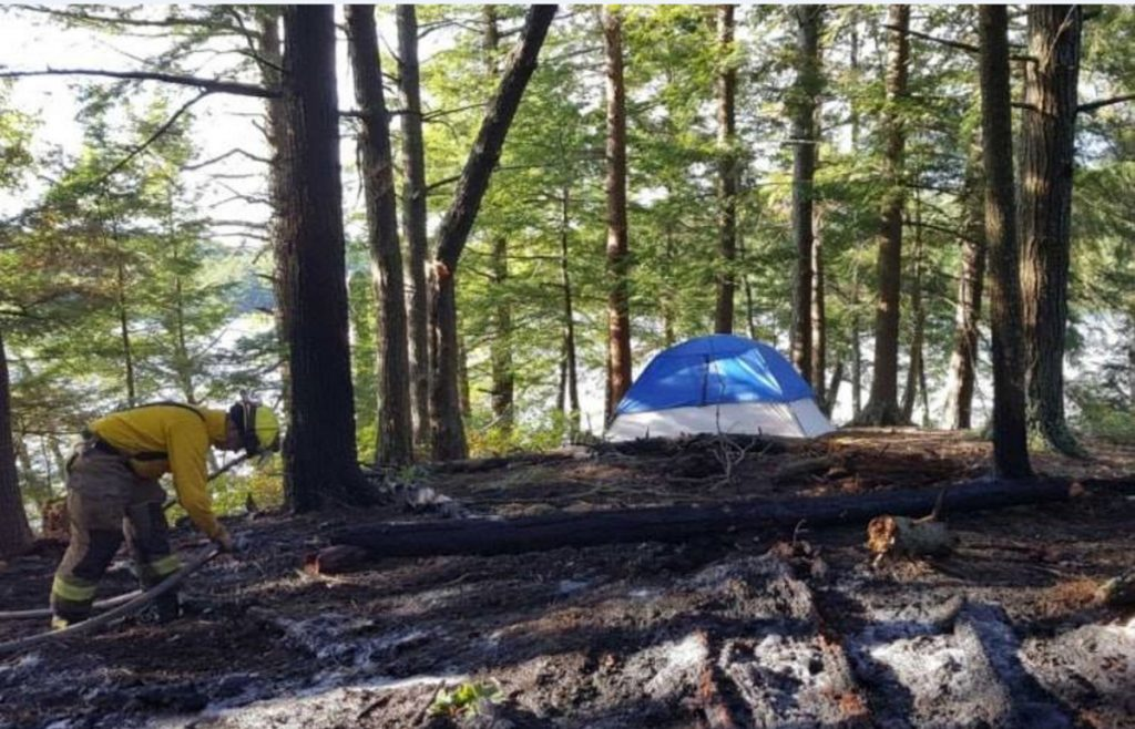 Members of the Belgrade Fire Department and Maine Forest Service knock down a fire near Hamilton Pond in Belgrade on Friday evening, July 13. Authorities say it resulted from an illegal campfire.