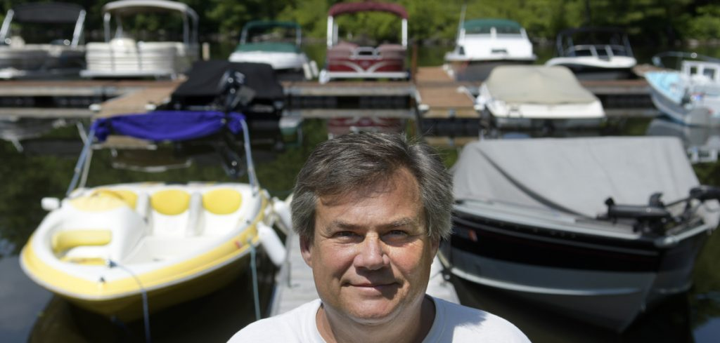 Shawn Grant stands Monday on the docks at Brightside Marina, the business he owns in Belgrade Lakes Village. Grant is appealing the denial of a commercial business permit for the marina he has operated on Hulin Road for 10 years.