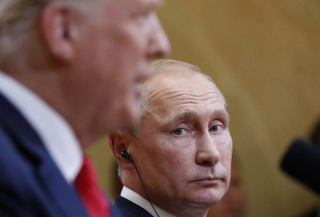 Russian President Vladimir Putin listens to U.S. President Donald Trump during a news conference Monday after the meeting in Helsinki, Finland. Trump tried to walk back some of his comments Tuesday.