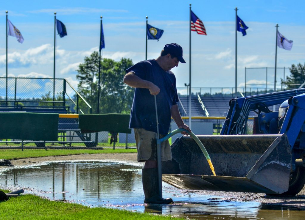 Staff photo by Joe Phelan Al Cloutier pumps water from a puddle on Wednesday on McGuire Field in Augusta. Workers were preparing for the 2018 New England Regional Babe Ruth Baseball 13-15 year-old Tournament that will start on Friday and run through Wednesday.