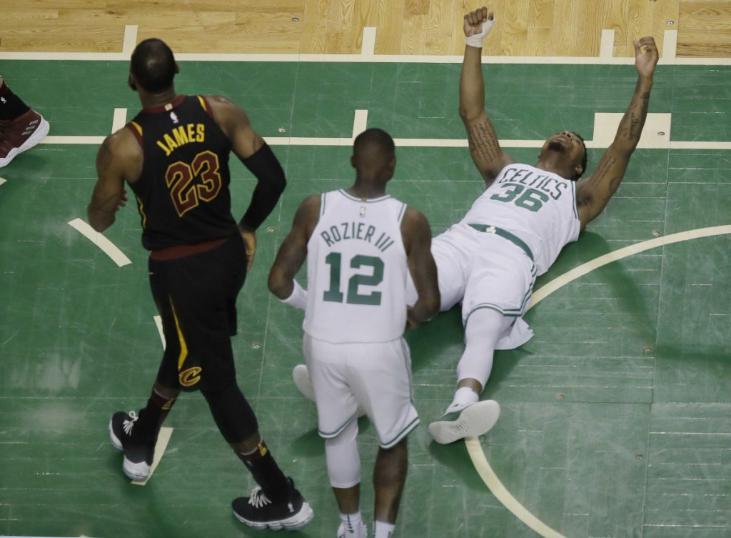 In this May 27 photo, Boston Celtics guard Marcus Smart (36) reacts after drawing an offensive foul by Cleveland Cavaliers forward LeBron James (23) during the first half in Game 7 of the Eastern Conference finals, in Boston. A person with knowledge of the agreement tells The Associated Press that Smart signed a four-year, $52 million contract with the Celtics.