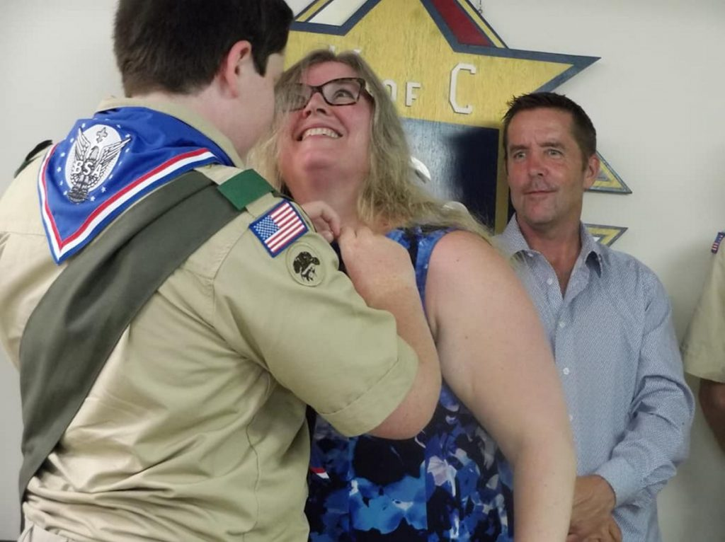 Eric McDonnell pins the Mother's Pin on his mom Audrey McDonnell in recognition of her support during his Scouting career while his dad Patrick looks on.
