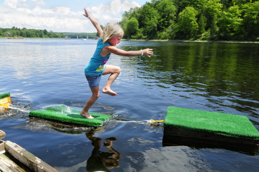 Emmy Foster, 7, of Richmond, scrambles over a string of floating lobster crates strung between two docks on July 23, 2016, in the Kennebec River as part of the town's annual Richmond Days festivities.