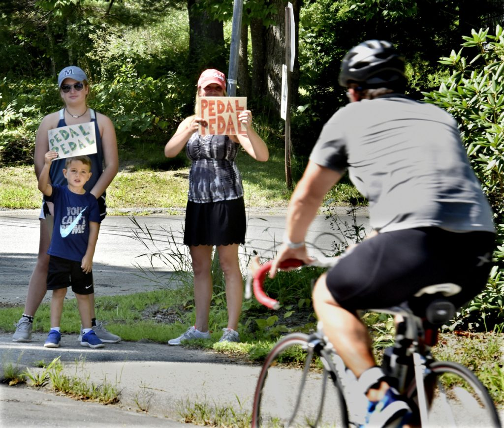 As a bike rider pedals by, Ellie Marden, left, brother Flynn and stepmother Jessica hold signs of support during  the Oakfest Paddle, Pedal, Pound Triathlon competition Sunday in Oakland.