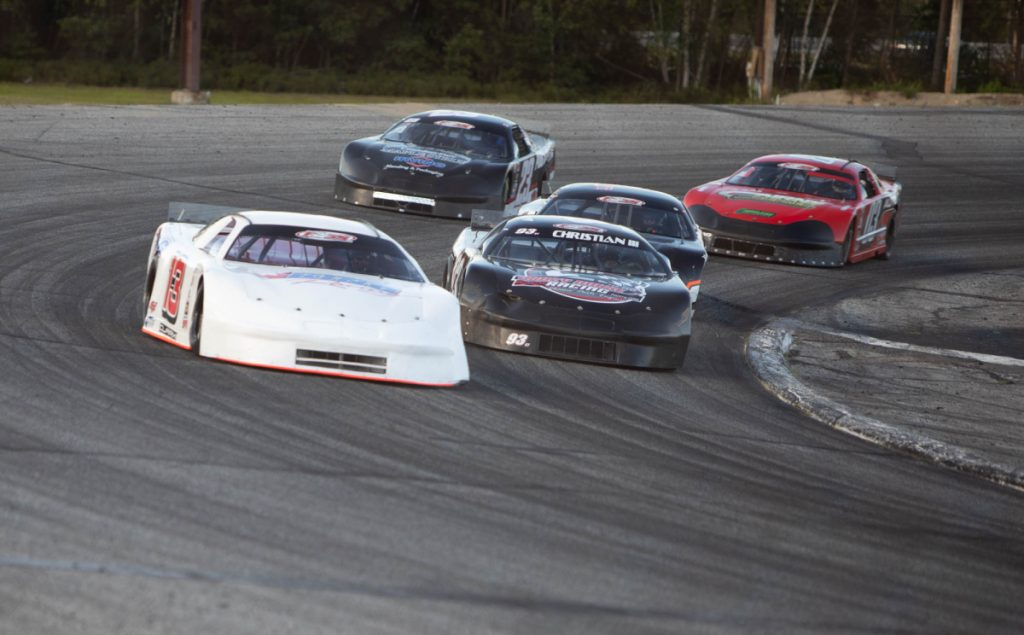 Cassius Clark, left, takes the lead ahead of Ray Christian during the PASS 150 on Sunday at Oxford Plains Speedway.