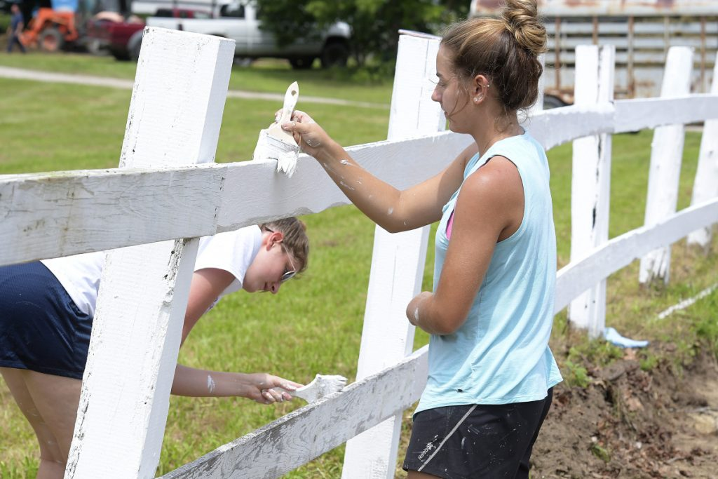 Kaeti Butterfield, left, and Abby Ferland whitewash a fence Tuesday near the horse pen at the Monmouth Fair as they touch up the border between the parking area and the pulling ring. The Monmouth Academy seniors were fulfilling a community service requirement to graduate. The Cochnewagon Agricultural Association's four-day annual fair opens Wednesday with a midway and animal exhibitions.