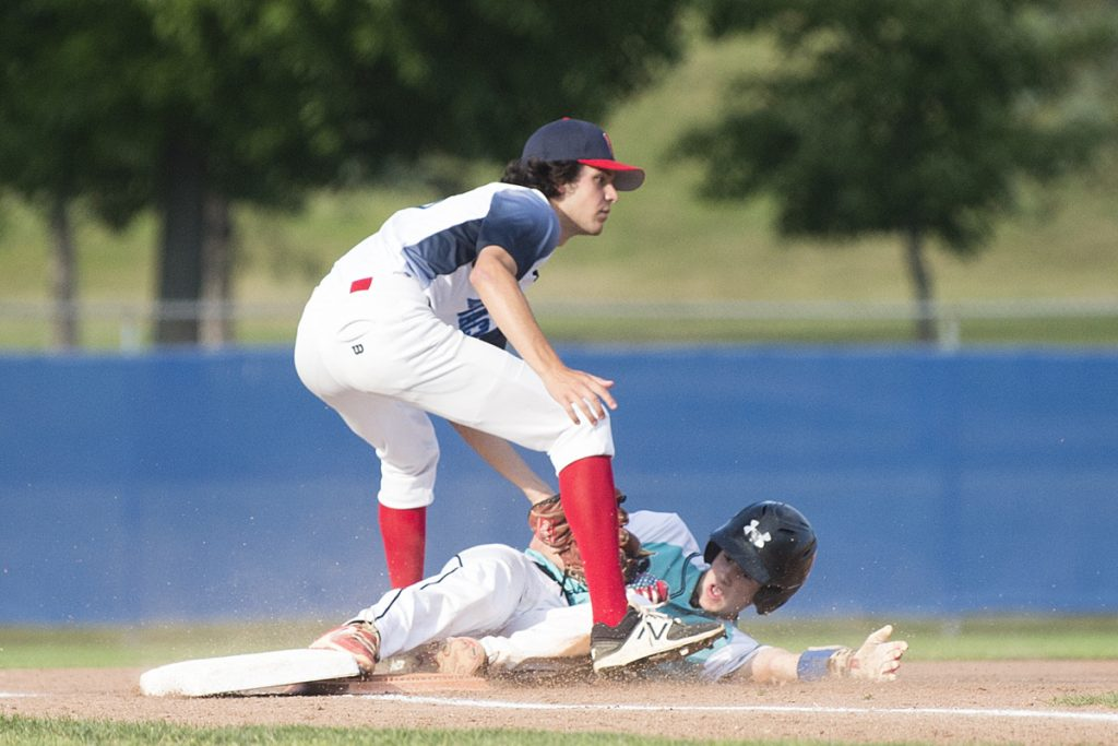 Staff photo by Michael G. Seamans   Messalonskee's Carter Lambert slides safely under the tag of Hampden's Michael Beaulieu at third base in the Junior American Legion State Tournament on Tuesday at Mansfield Stadium in Bangor.