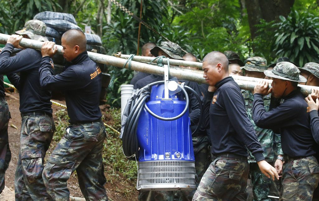 Soldiers carry a pump Friday to help drain the  floodwater in a cave where 12 boys and their soccer coach have been trapped since June 23.. More rains are forecast to hit the region within days.