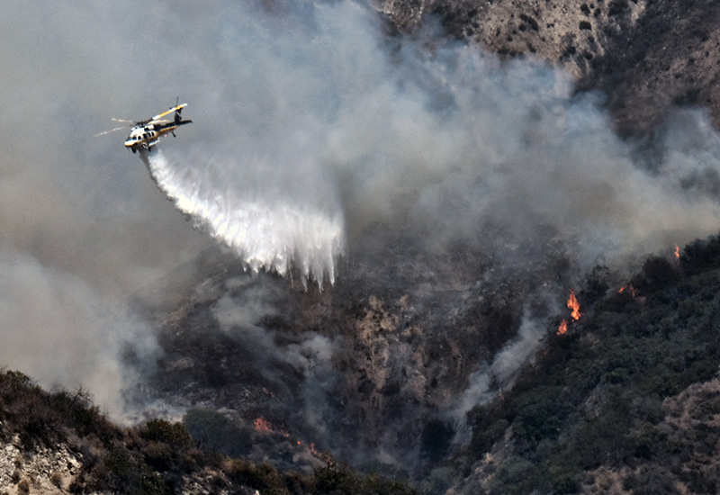 A Los Angeles County Fire Department helicopter drops water on a brush fire that erupted on a mountainside above suburban Burbank, Calif. on Saturday.