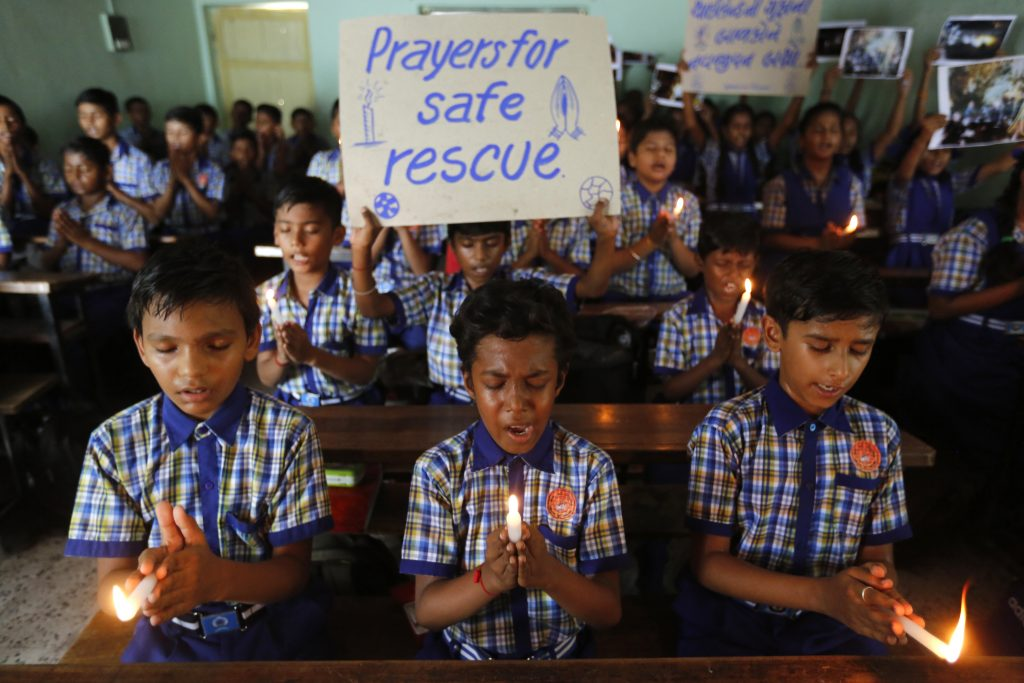 Indian students hold candles and pray Monday for boys and their soccer coach who have been trapped since June 23, in Mae Sai, Chiang Rai province, northern Thailand, at a school in Ahmadabad, India.