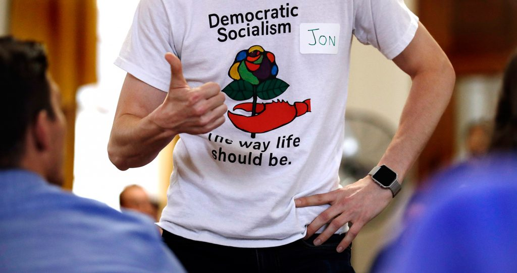 Jon Torsch, center, wears a T-shirt promoting democratic socialism during a gathering of the Southern Maine Democratic Socialists of America at City Hall in Portland.