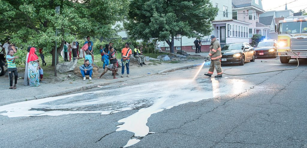 A Lewiston firefighter hoses down blood stains Monday evening on Blake Street near Maple Street after a man was assaulted and taken to a hospital. Police had a good description of the suspect and were searching for him late Monday.