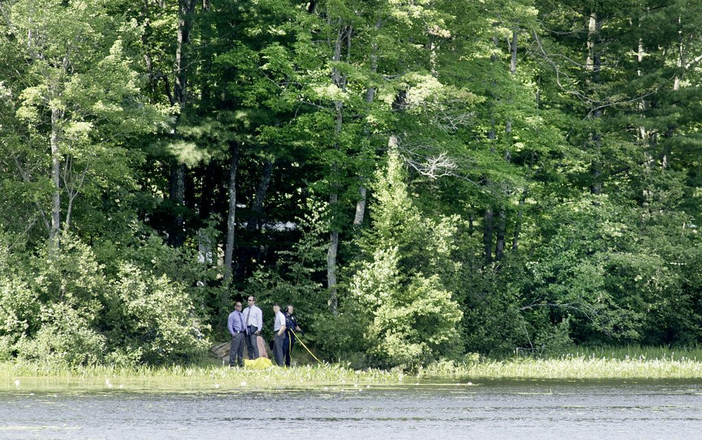 Officers with the Auburn Police Department and the Maine State Police Major Crime Unit investigate a death after a body was discovered near the shoreline of The Basin along Holbrook Road in Auburn on Sunday morning. A diver is being assisted by the officer at right with a yellow line.