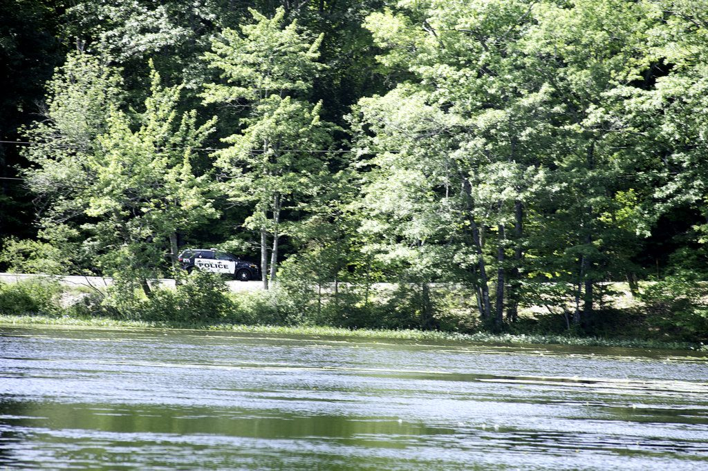 An officer with the Auburn Police Department drives down the Holbrook Road alongside The Basin on Sunday morning. (