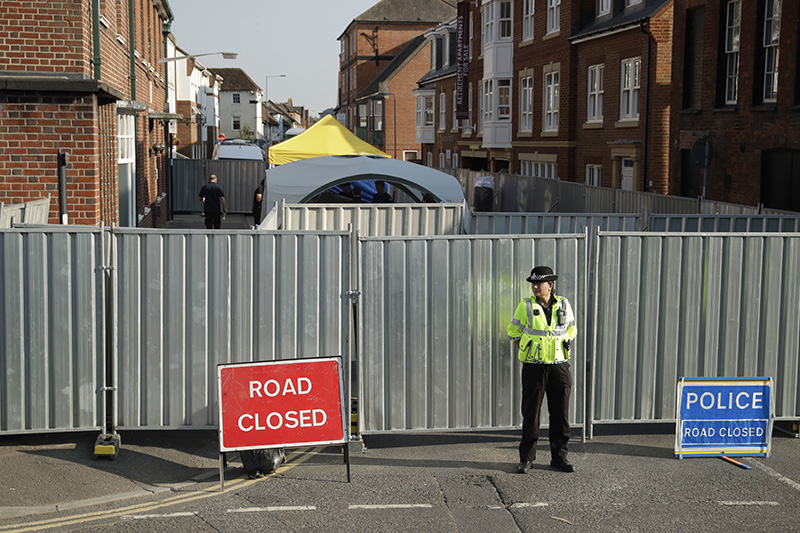 A police officer guards metal fencing erected as tents are set up behind where two people cam in contact with a deadly nerve agent.,  in Salisbury, England.
