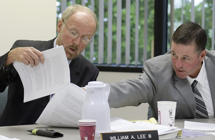 From left, Maine ethics commission members Richard Nass, William Lee III and Bradford A. Pattershall examine a document in July while hearing a Clean Elections complaint from House District 110 candidate Mark André in Augusta.
