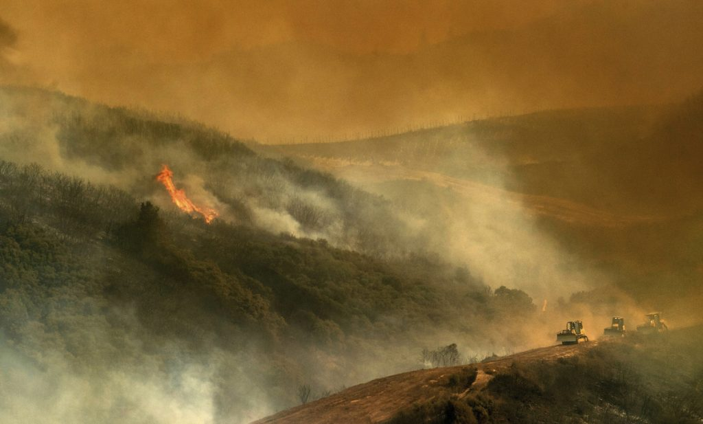 Bulldozers build containment lines against a wildfire in this week in Lakeport, Calif., one of multiple blazes that has caused the state to exhaust one-quarter of its fire budget.