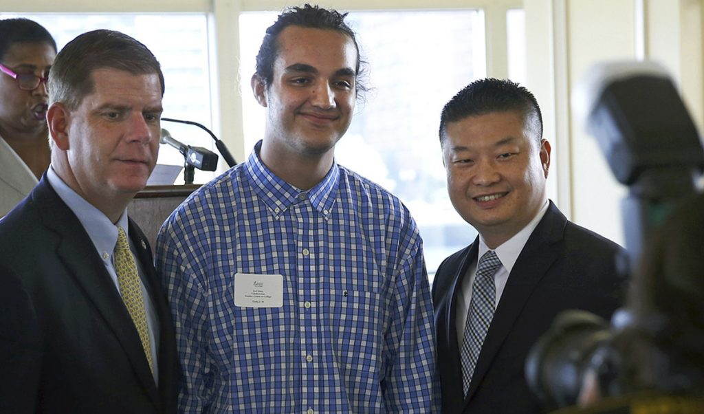 Joel Ortiz, center, poses with Mayor Marty Walsh, left, and school Superintendent Tommy Chang at a lunch for school valedictorians in Boston in 2016. Ortiz was arrested on July 12 on suspicion of hacking personal cell phones and stealing millions of dollars in digital currency.