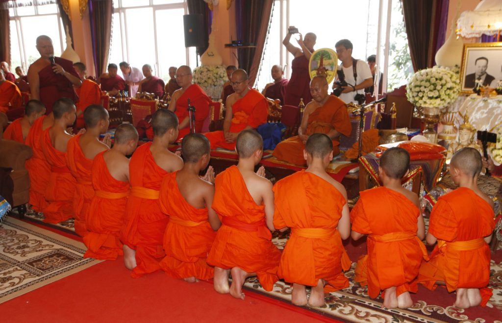 Members of the Wild Boars soccer team pray Saturday as they complete service as novice Buddhist monks.