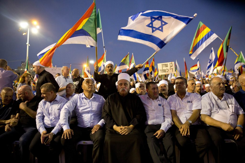 Druze spiritual leader Sheik Mowafaq Tafik, center, sits during a rally against Israel's Jewish Nation bill in Tel Aviv on Saturday.