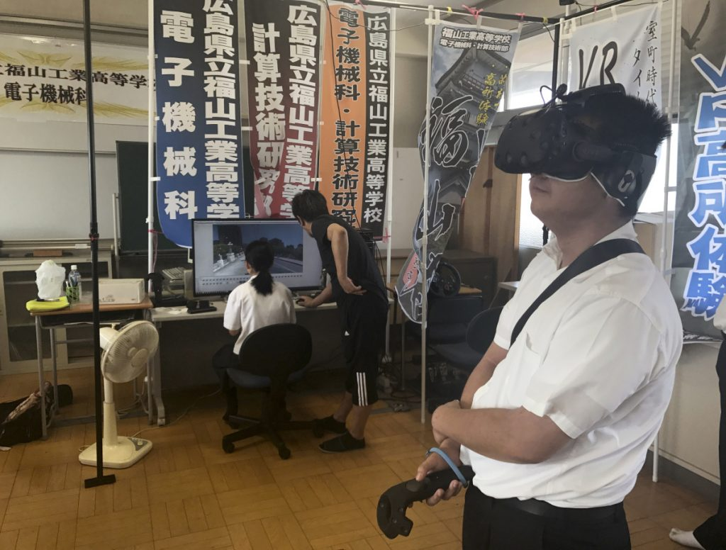 In Friday, Aug. 8, 2018, photo, Namio Matsura, right, a 17-year-old member of the computation skill research club at Fukuyama Technical High School, watches Hiroshima city before atomic bomb fell in virtual reality experience as Katsushi Hasegawa, a computer teacher, and Mei Okada, another member of the club, watch a computer screen, at the school in Hiroshima, western Japan. Over two years, the group of Japanese high school students has been painstakingly producing a five-minute virtual reality experience that recreates the sights and sounds of Hiroshima before, during and after the U.S. dropped an atomic bomb on the city 73 years ago. (AP Photo/Haruka Nuga)