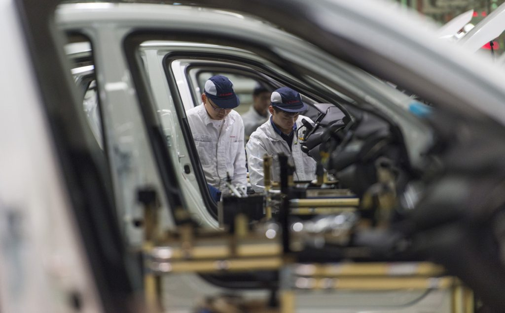 Workers assemble cars at the Dongfeng Honda automotive plant in Wuhan in central China's Hubei province in this 2017 photo. China's auto sales shrank by 5.3 percent in July 2018 from a year earlier, signaling economic malaise amid a tariff battle with Washington.