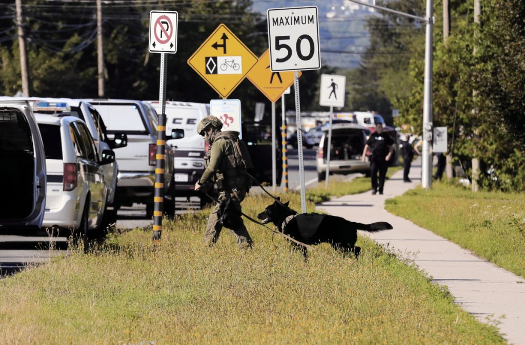 Police officers survey the area of a shooting in Fredericton, New Brunswick, on Friday.  Fredericton police say two officers were among four people who died in a shooting in a residential area on the city's north side.