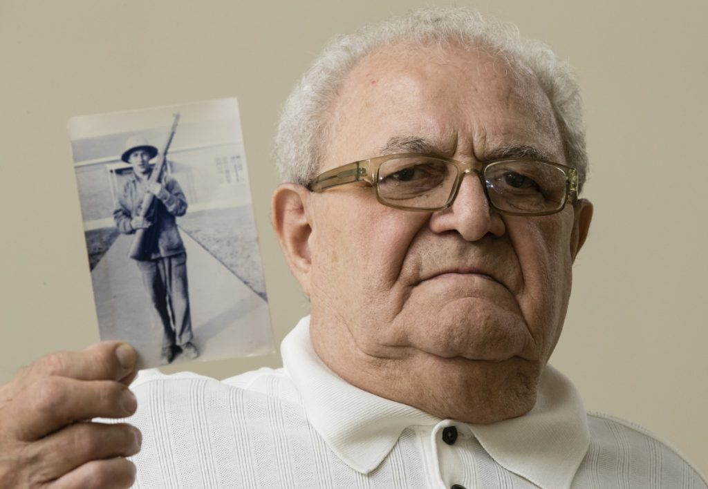 Dominic Ragucci poses for a portrait in Philadelphia with a photo of his brother, Emil, who was killed in action on the Central Pacific island of Tarawa during World War II.