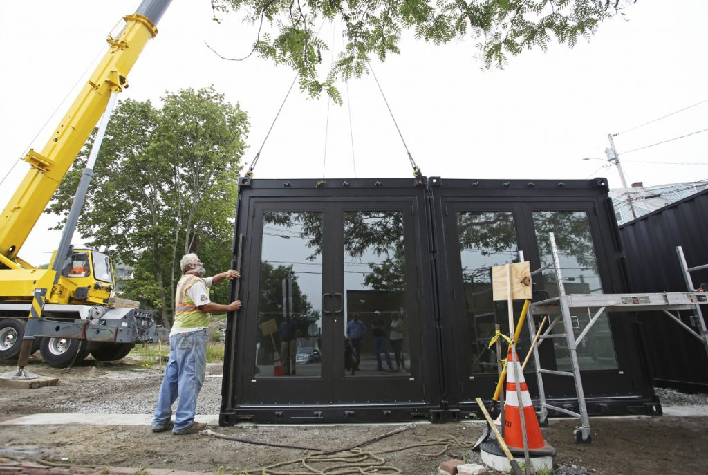 John Anderson uses a level Monday as entry doors are placed on modified shipping containers at 93 Washington St. in Portland. The five containers, pre-built by SnapSpace Solutions in Brewer, will hold five retail storefronts, allowing businesses to experiment without long-term lease commitments.